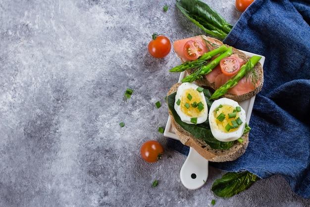 Два сэндвича со шпинатом, вареными яйцами и соленым лососем, помидорами черри и зеленой спаржей