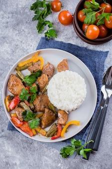 灰色の石のテーブル背景に皿にご飯と野菜をチキンします。アジアンタイ料理