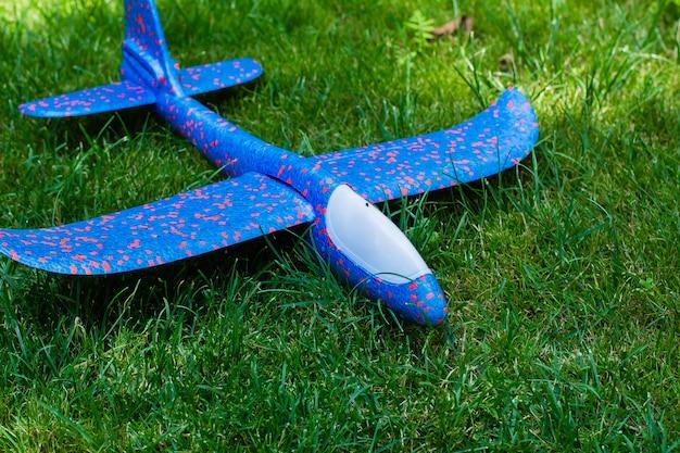 旅行、旅行、休暇の概念。緑の芝生の上の飛行機。子供のおもちゃ緑の自然の背景。