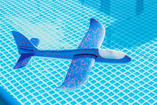 旅行、旅行、休暇の概念。プール内の水に飛行機。子供のおもちゃ