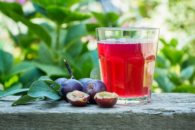 Сливовый сок в стакан на фоне деревянный стол. естественный фон зеленый лист. копировать пространство