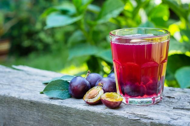 Сливовый сок в стакан на фоне деревянный стол. естественный фон зеленый лист. скопируйте сок.