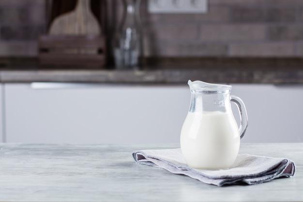 キッチンのコンクリートテーブルの背景にミルクの水差し。乳製品。コピースペース