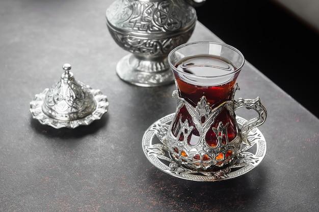 Турецкий чай в традиционном стакане на темном столе