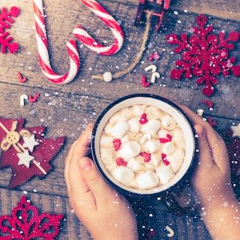 ホットチョコレートカップを保持する女の子。クリスマスホリデーカード。