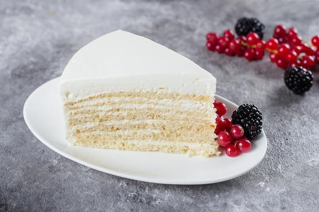 Кусок «молочной девочки» торт на тарелку с ягодами на бетонный серый стол. копировать пространство