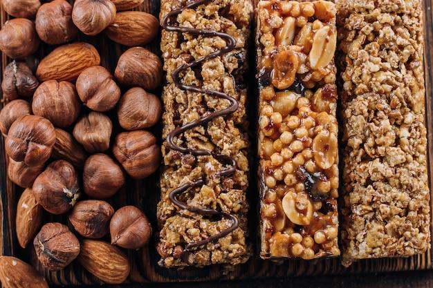健康バーとナッツの背景アーモンドとヘーゼルナッツのエネルギーバー。健康的な静物のための軽食