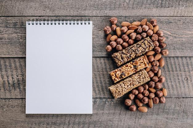 健康バー、ミックスナッツ、テキスト用の空白のノートブックの空白。アーモンドとヘーゼルナッツのエネルギーバー