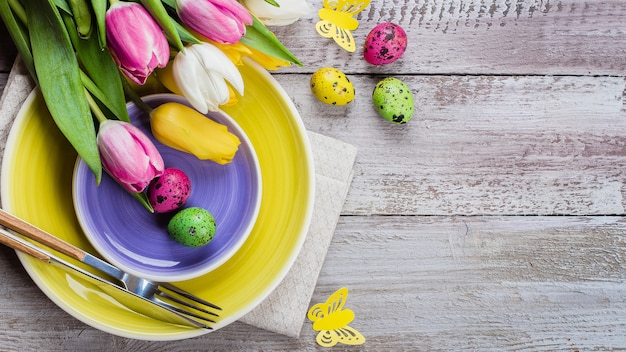 Пасхальная сервировка с весенними тюльпанами и столовыми приборами. праздники фон. вид сверху, плоская планировка