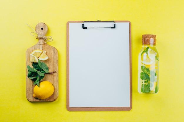 Идея проекта доски зажима модель-макета и воды мяты лимона на желтой предпосылке.
