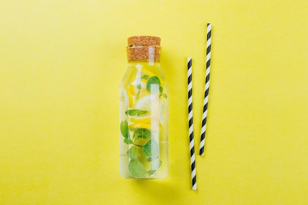 黄色のテーブル背景にガラス瓶と紙管のレモネード。夏の飲み物のコンセプト