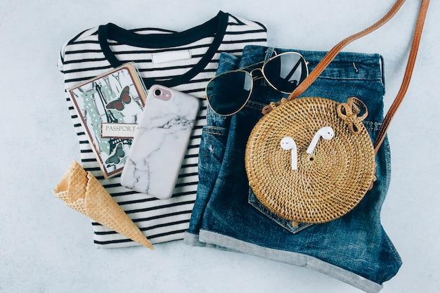 Футболка в полоску, синие джинсовые шорты, модная сумка из органического ротанга. отпуск, концепция путешествия.