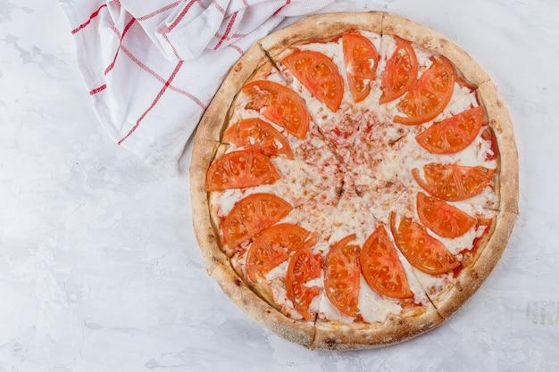 イタリア料理。ピザマルゲリータマルガリータチーズ、背景にトマトソース。