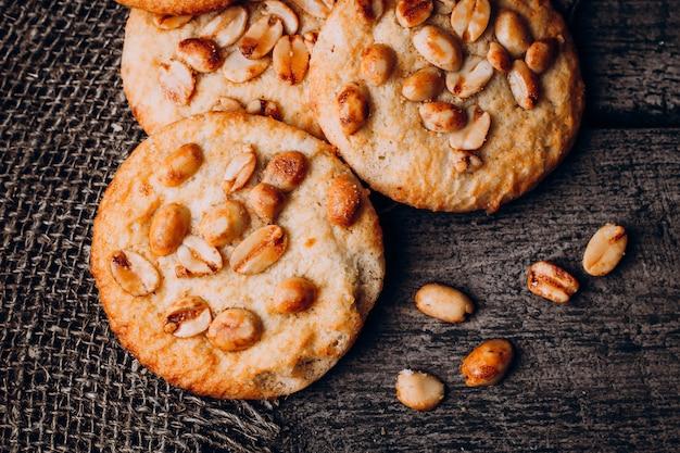 Закройте вверх по печеньям овсяной каши с арахисами на темной деревянной таблице предпосылки. вид сверху крупным планом
