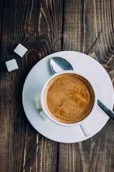 Свежая чашка кофе и сахар на старой деревенской предпосылке таблицы. утренняя концепция