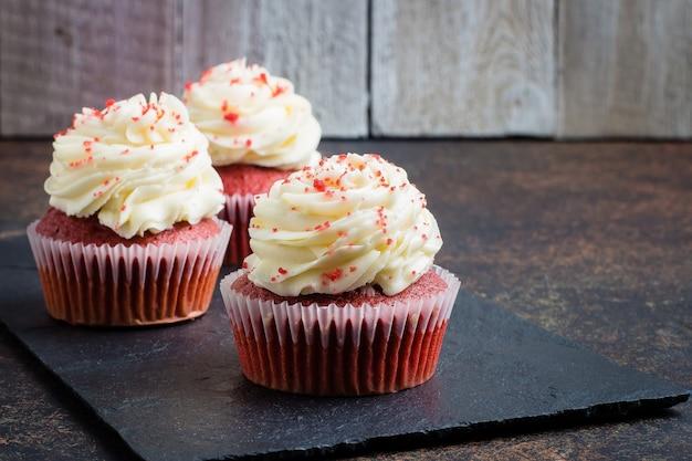暗い石のテーブル背景にスレート板に赤いベルベットのカップケーキ。休日のデザート