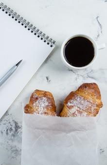 クロワッサンと空のノートブックと事業計画とデザインのアイデアのためのペンとコーヒー・マグ
