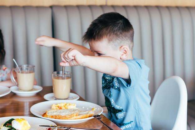 朝食を食べて面白いと幸せな少年。カフェの窓の近くの軽いブランチ。パン、オムレツ、お茶