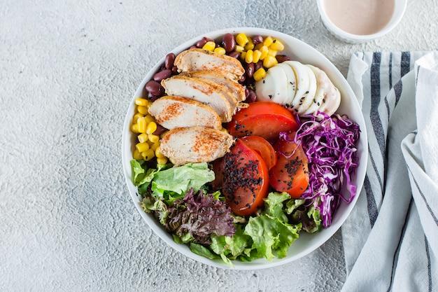 ボウルにバランスの取れた昼食。健康食品のコンセプトです。明るいコンクリートの背景。