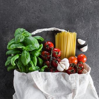 食料品の再利用可能なバッグ。トートバッグ、最小限の無駄。バジル、チェリートマト、ニンニク、生地の袋