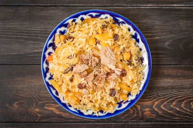 国立食品-暗い木製のテーブルの上面に伝統的なパターンを持つプレートの肉とウズベキスタンのピラフトップビューフラットレイアウトラマダン、ナウルズの休日の概念