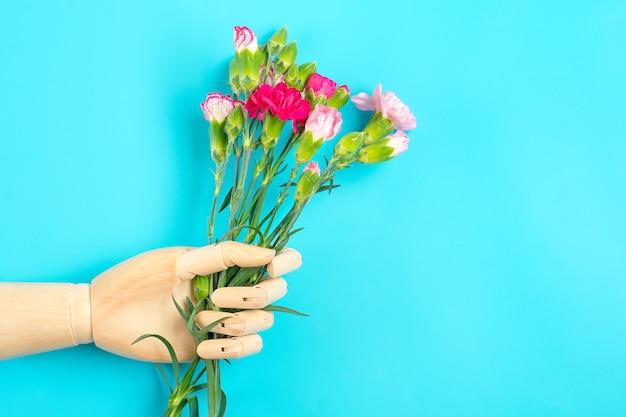 木製の手が青色の背景に別のピンクのカーネーションの花の花束を保持しますトップビューフラットレイアウト