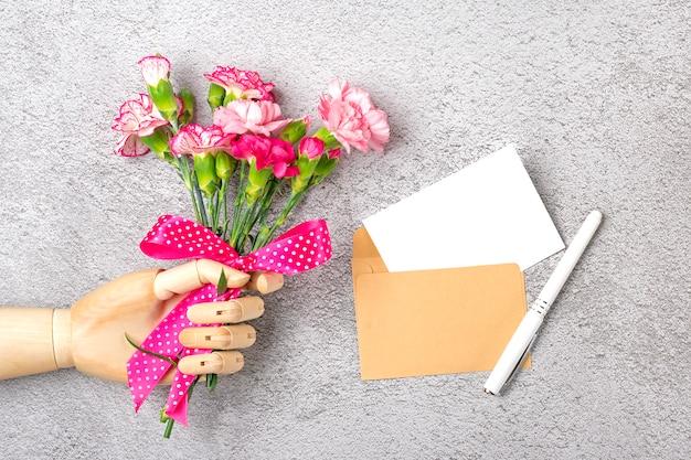 木製の手を保持する別のピンクのカーネーションの花、クラフト封筒、灰色の背景に分離された紙のカラフルな花束