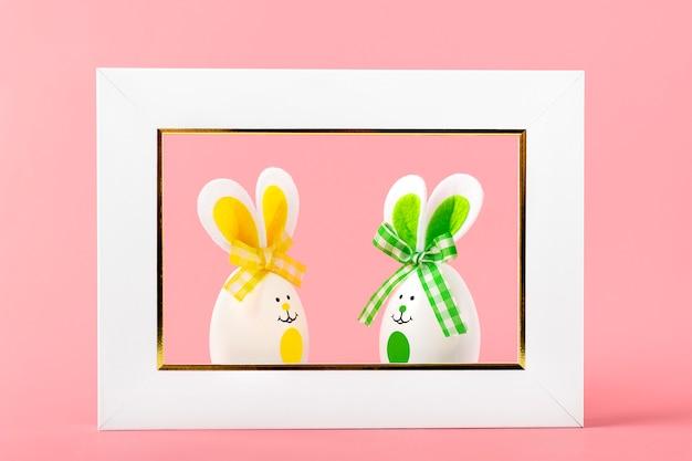 Окрашенные пасхальные яйца милый зайчик с улыбкой лица, уши, лук и белая фоторамка на кораллово-розовый фон.