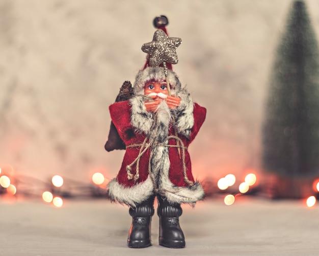 サンタクロースのおもちゃは、背景に星とクリスマスツリーのスタッフを保持しています
