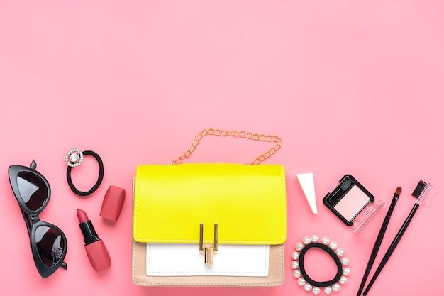 ピンクのテーブルに女性のアクセサリーと黄色のハンドバッグ