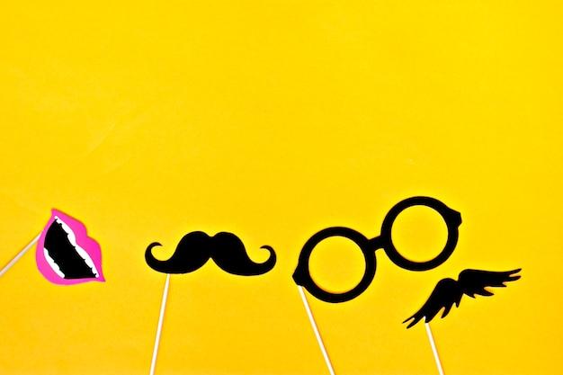 Усы, галстук, очки, красный рот на деревянных палочках на фоне ярко-желтого цвета