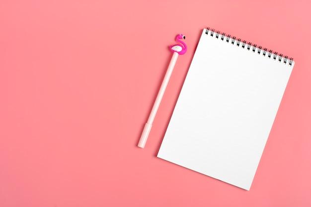 白いメモ帳、クリップ、フラミンゴの形のペン、ピンクの背景