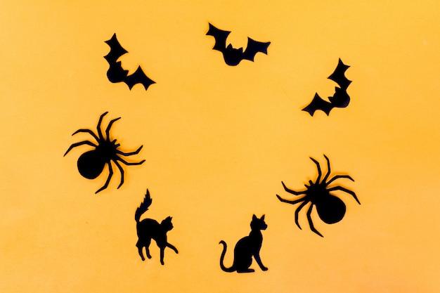 ハロウィーンを祝うための工芸品。スパイダーフィギュア、猫、黄色の背景に黒い紙からのバット