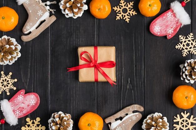 Рождественский декор коньки, варежки, снежинки, мандарины, шишки, коробка на деревянном фоне плоская планировка