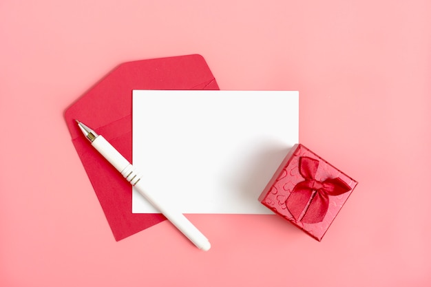 メッセージ、赤い封筒、ギフト用の箱、ペン、ピンクの背景の紙の白いシート。幸せなバレンタインデー