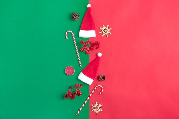 クリスマスの装飾の贈り物、サンタクロースの帽子、キャンディー、緑の背景に雪片。フラットレイ