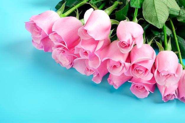 青い背景にピンクのバラ。