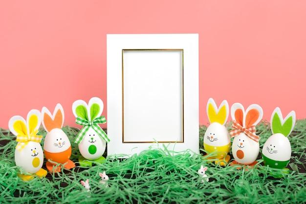 イースターエッグかわいいウサギ、草、珊瑚ピンクの背景に白のフォトフレーム。