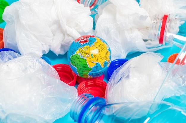 透明、ビニール袋、蛍光灯、地球のペットボトルの背景。フラットレイ