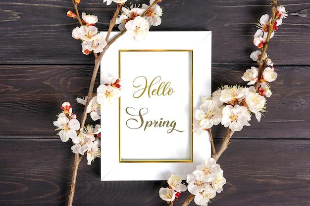 白いフォトフレームと木製の背景に花と杏の木の小枝。
