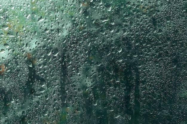 窓に雨のビューが値下がりしました。秋、春の季節、天気の概念。