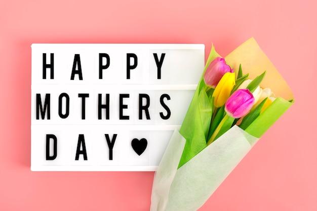 引用とライトボックス幸せな母の日、ピンクの背景に色とりどりのチューリップ。