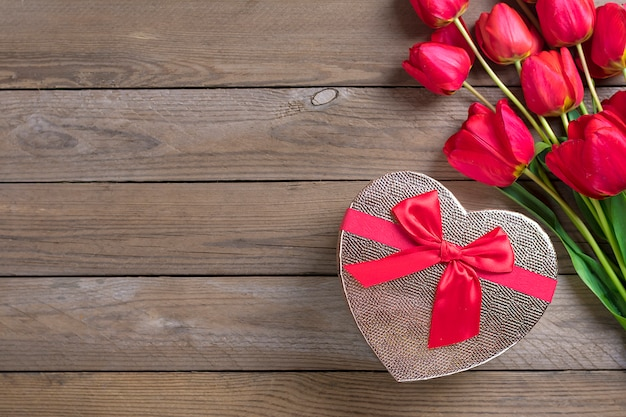 テキスト、メッセージ用のスペースと木製の背景に赤いチューリップ。母の日、こんにちは春のコンセプトです。