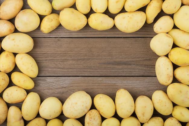 木製のテーブルの上の若いジャガイモ。素朴なスタイル上面図。平らに置きます。