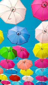 カラフルなパラソルの背景。空にカラフルな傘。ストリートデコレーション