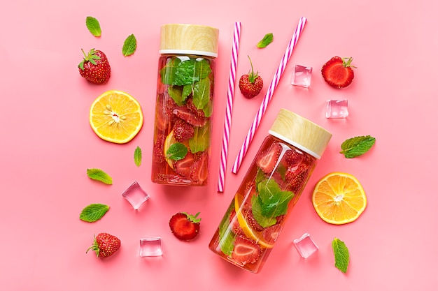 夏はイチゴ、レモン、ピンクの背景にミントの葉を飲みます。