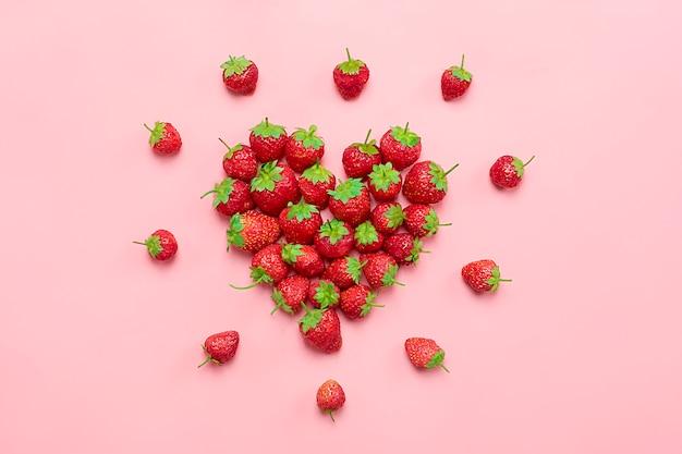 トレンドピンクの背景に、豪華なジューシーなイチゴから作られた心