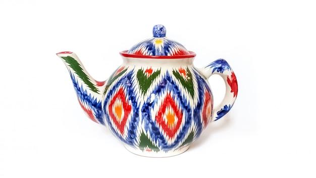 伝統的なウズベキスタンの器具 - 白で隔離される飾りイカットとやかん