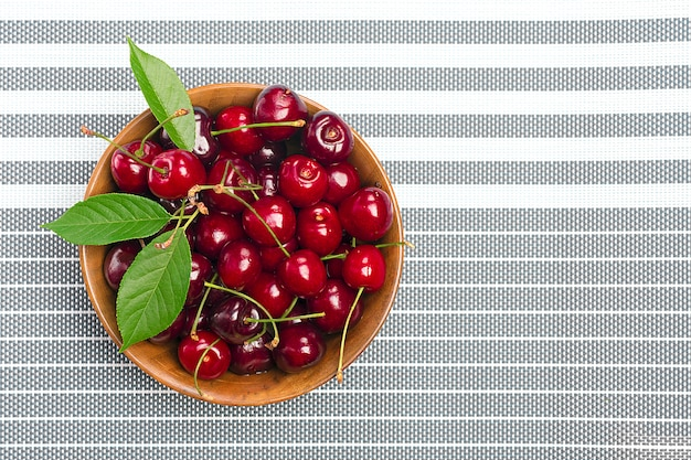 Сырая свежая вишня в деревянной миске