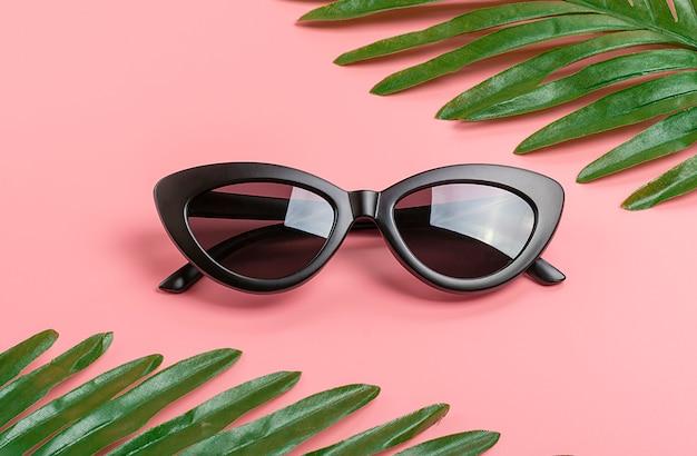 黒眼鏡と緑のヤシの葉のトレンディなピンク
